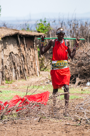 AMBOSELI, KENYA - OCTOBER 10, 2009: Unidentified Massai woman walks wearing typical tribal red clothes and carring   a rocker for water in Kenya, Oct 10, 2009. Massai people are a Nilotic ethnic group Standard-Bild - 112568782
