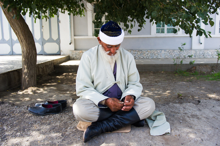BUKHARA, UZBEKISTAN - JUNE 7, 2011: Unidentified Uzbek man sits on the ground in Uzbekistan, Jun 7, 2011.  81% of people in Uzbekistan belong to Uzbek ethnic group Editorial