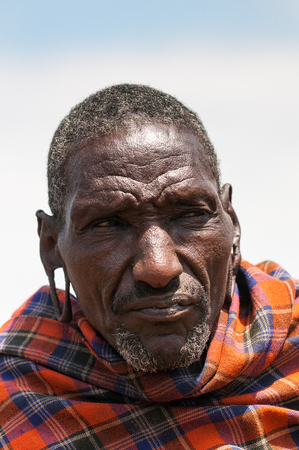 AMBOSELI, KENYA - OCTOBER 10, 2009: Portrait of an unidentified old serious Massai wearing typical tribal clothes in Kenya, Oct 10, 2009. Massai people are a Nilotic ethnic group Standard-Bild - 113977913