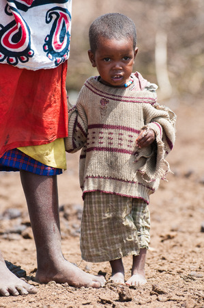 AMBOSELI, KENYA - OCTOBER 10, 2009: Unidentified Massai little baby girl in old clothes holds her mothes skirtin Kenya, Oct 10, 2009. Massai people are a Nilotic ethnic group Standard-Bild - 113977941