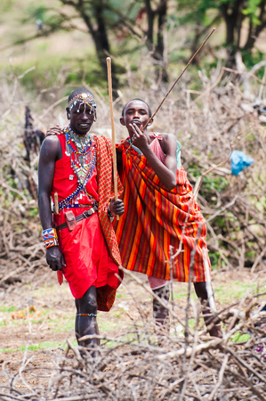 KENYA - OCTOBER 10, 2009: Unidentified Massai husband and wife waving and smiling for the camera in Kenya, Oct 10, 2009. Massai people are a Nilotic ethnic group Standard-Bild - 113977945