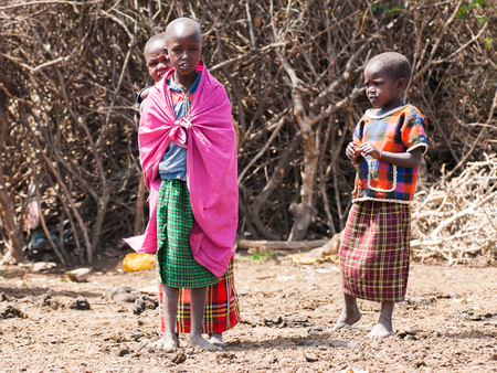 AMBOSELI, KENYA - OCTOBER 10, 2009: Unidentified Massai woman and children wearing tribal typical clothes in Kenya, Oct 10, 2009. Massai people are a Nilotic ethnic group Standard-Bild - 113977994