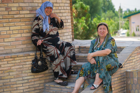 TASHKENT, UZBEKISTAN - JUNE 12, 2011: Two ladies sit and talk in the street in Uzbekistan, Jun 12, 2011.  81% of people in Uzbekistan belong to Uzbek ethnic group