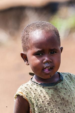 AMBOSELI, KENYA - OCTOBER 10, 2009: Portait of an unidentified Massai little baby girl in dirty dress in Kenya, Oct 10, 2009. Massai people are a Nilotic ethnic group Standard-Bild - 113978153