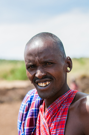 KENYA - OCTOBER 10, 2009: Portrait of an unidentified Massai smiling man in typical tribal clothes in Kenya, Oct 10, 2009. Massai people are a Nilotic ethnic group Standard-Bild - 113978057
