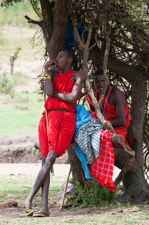 AMBOSELI, KENYA - OCTOBER 10, 2009: Unidentified Massai people near the tree in Kenya, Oct 10, 2009. Massai people are a Nilotic ethnic group Standard-Bild - 113978063