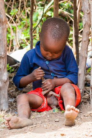KENYA - OCTOBER 10, 2009: Unidentified Massai little boy plays with an elephant toy in Kenya, Oct 10, 2009. Massai people are a Nilotic ethnic group Standard-Bild - 113978072