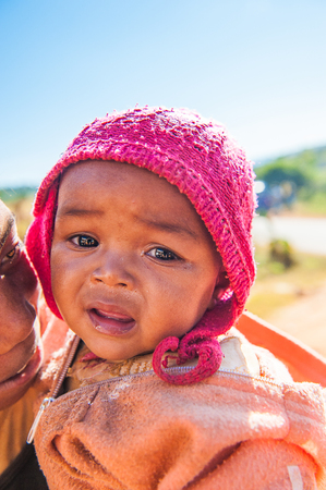 MADAGASCAR - JULY 1, 2011: Portrait of an unidentified little girl on her mother arms in Madagascar, July 1, 2011. Children of Madagascar suffer of poverty due to the unstable situation. 新闻类图片