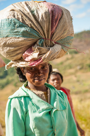 ANTANANARIVO, MADAGASCAR - JUNE 30, 2011: Unidentified Madagascar woman carries carries a big bag the street. People in Madagascar suffer of poverty due to slow development of the country Stock Photo - 114719447