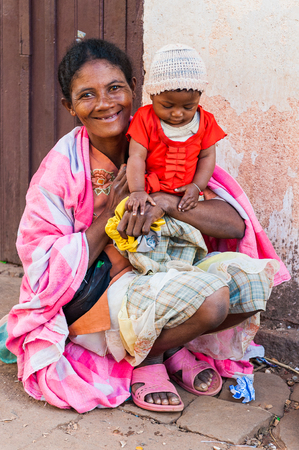 ANTANANARIVO, MADAGASCAR - JUNE 30, 2011: Unidentified Madagascar woman holds her little baby. People in Madagascar suffer of poverty due to slow development of the country