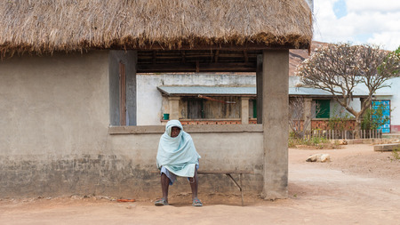 ANTANANARIVO, MADAGASCAR - JULY 1, 2011: Unidentified Madagascar woman sits near the house. People in Madagascar suffer of poverty due to slow development of the country Editorial