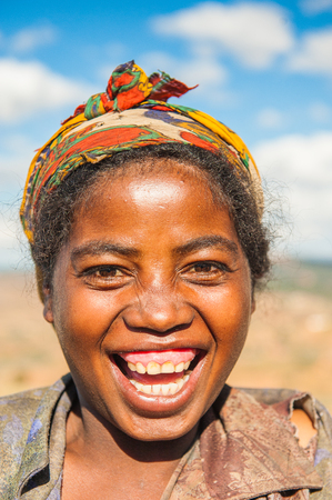 MADAGASCAR - JUNE 30, 2011: Portrait of an unidentified smiling woman working in the field in Madagascar, June 30, 2011. People of Madagascar suffer of poverty due to the unstable situation.