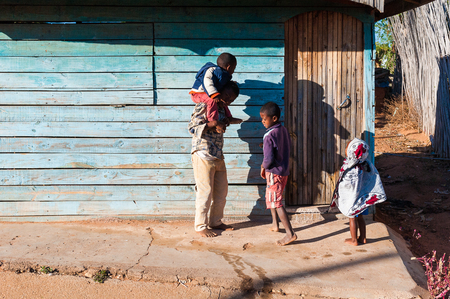 ANTANANARIVO, MADAGASCAR - JULY 3, 2011: Unidentified Madagascar father and his children in the street. People in Madagascar suffer of poverty due to slow development of the country Stock Photo - 114099746