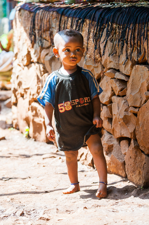OMO, ETHIOPIA - SEPTEMBER 20, 2011: Unidentified Ethiopian beautiful boy in a T-shirt near a stone wall. People in Ethiopia suffer of poverty due to the unstable situation