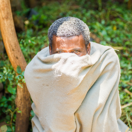 OMO, ETHIOPIA - SEPTEMBER 20, 2011: Unidentified Ethiopian specific man wearing white cloack and hides his face. . People in Ethiopia suffer of poverty due to the unstable situation Editorial
