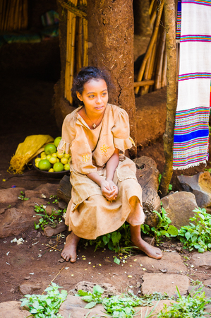OMO, ETHIOPIA - SEPTEMBER 20, 2011: Unidentified Ethiopian beautiful girl smiles near a house porch. People in Ethiopia suffer of poverty due to the unstable situation