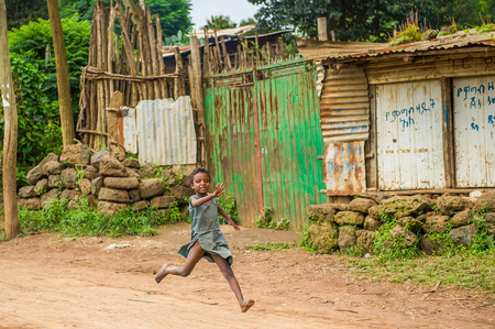 OMO, ETHIOPIA - SEPTEMBER 19, 2011: Unidentified Ethiopian girl runs happily. People in Ethiopia suffer of poverty due to the unstable situation