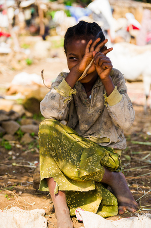OMO, ETHIOPIA - SEPTEMBER 20, 2011: Unidentified Ethiopian smiling girl shuts her face with a hand. People in Ethiopia suffer of poverty due to the unstable situation 新聞圖片