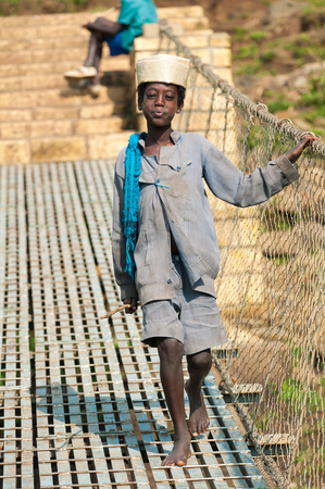 OMO, ETHIOPIA - SEPTEMBER 20, 2011: Unidentified Ethiopian girl walks over the rope bridge. People in Ethiopia suffer of poverty due to the unstable situation