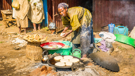 OMO, ETHIOPIA - SEPTEMBER 19, 2011: Unidentified Ethiopian woman makes pancakes at the local market. People in Ethiopia suffer of poverty due to the unstable situation