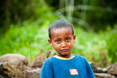 OMO, ETHIOPIA - SEPTEMBER 22, 2011: Unidentified Ethiopian cute little boy smiles wearing the blue jersey. People in Ethiopia suffer of poverty due to the unstable situation