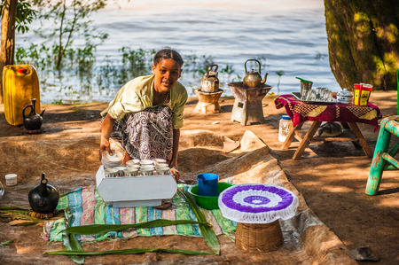 OMO, ETHIOPIA - SEPTEMBER 20, 2011: Unidentified Ethiopian woman with dishes and cup. People in Ethiopia suffer of poverty due to the unstable situation 報道画像