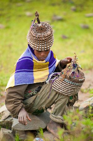 AKSUM, ETHIOPIA - SEPTEMBER 22, 2011: Unidentified Ethiopian boy sells the traditional hat with the green nature background. People in Ethiopia suffer of poverty due to the unstable situation Editorial