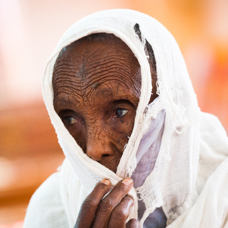 AKSUM, ETHIOPIA - SEP 24, 2011: Unidentified Ethiopian old woman wearing white tissue in Ethiopia, Sep.24, 2011. People in Ethiopia suffer of poverty due to the unstable situation Redactioneel