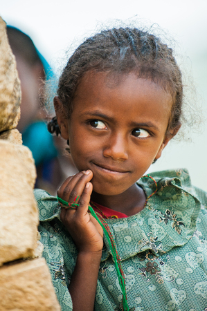 AKSUM, ETHIOPIA - SEP 24, 2011: Unidentified Ethiopian cute little girl in green dress near the stone wall in Ethiopia, Sep.24, 2011. Children in Ethiopia suffer of poverty due to the unstable situation Editorial