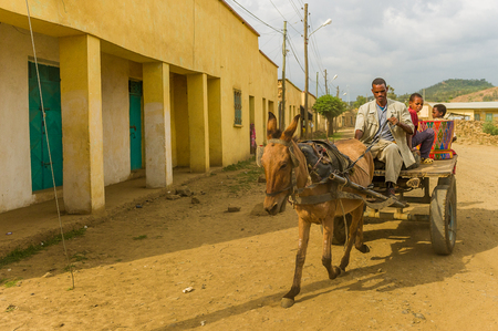 OMO, ETHIOPIA - SEPTEMBER 21, 2011: Unidentified Ethiopian men on a horse carriage in the street. People in Ethiopia suffer of poverty due to the unstable situation