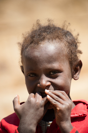 AKSUM, ETHIOPIA - SEP 24, 2011: Unidentified Ethiopian beautiful girl biting the fingers in Ethiopia, Sep.24, 2011. Children in Ethiopia suffer of poverty due to the unstable situation