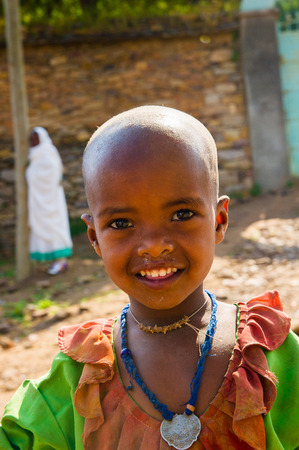 AKSUM, ETHIOPIA - SEP 24, 2011: Unidentified Ethiopian little girl in bright national dress in Ethiopia, Sep.24, 2011. Children in Ethiopia suffer of poverty due to the unstable situation