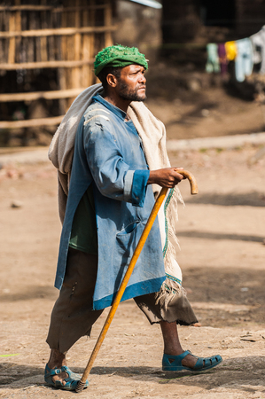 AKSUM, ETHIOPIA - SEPTEMBER 24, 2011: Unidentified Ethiopian man walks quickly with a baston. People in Ethiopia suffer of poverty due to the unstable situation Editorial
