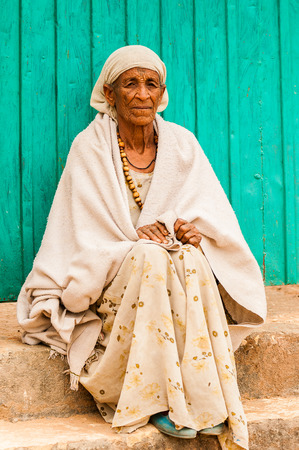 AKSUM, ETHIOPIA - SEPTEMBER 24, 2011: Unidentified Ethiopian beautiful woman in white tissue sits at the porch of the house. People in Ethiopia suffer of poverty due to the unstable situation