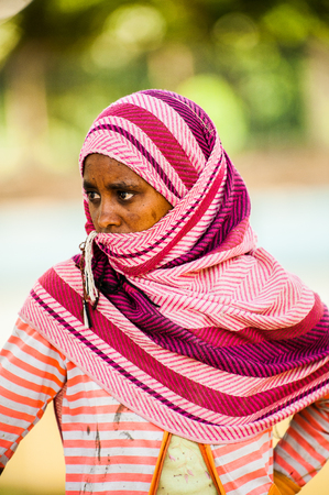 AKSUM, ETHIOPIA - SEPTEMBER 24, 2011: Unidentified Ethiopian woman wears tissue and shuts her face. People in Ethiopia suffer of poverty due to the unstable situation