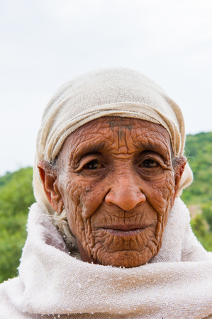 AKSUM, ETHIOPIA - SEP 24, 2011: Unidentified Ethiopian old woman in white clothes in Ethiopia, Sep.24, 2011. People in Ethiopia suffer of poverty due to the unstable situation