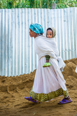 OMO, ETHIOPIA - SEPTEMBER 21, 2011: Unidentified Ethiopian woman in white tissue with a baby. People in Ethiopia suffer of poverty due to the unstable situation Editorial