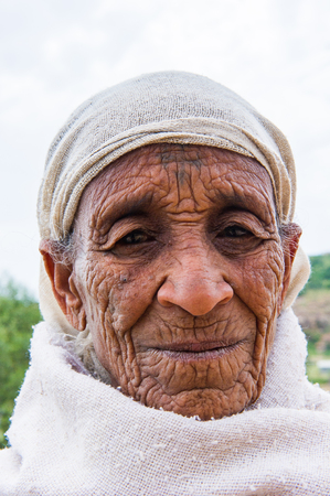 AKSUM, ETHIOPIA - SEP 24, 2011: Unidentified Ethiopian old woman in white clothes in Ethiopia, Sep.24, 2011. People in Ethiopia suffer of poverty due to the unstable situation Banque d'images - 114035732