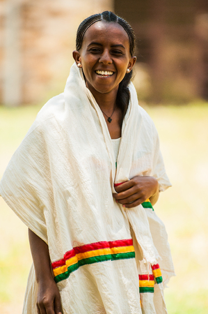 AKSUM, ETHIOPIA - SEPTEMBER 24, 2011: Unidentified Ethiopian girl smiles in a white tissue with national colors of Ethiopia. People in Ethiopia suffer of poverty due to the unstable situation 新闻类图片