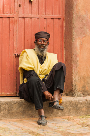 AKSUM, ETHIOPIA - SEPTEMBER 24, 2011: Unidentified Ethiopian funny smiling man wears his shoes sitting at the porch of his house. People in Ethiopia suffer of poverty due to the unstable situation 新闻类图片