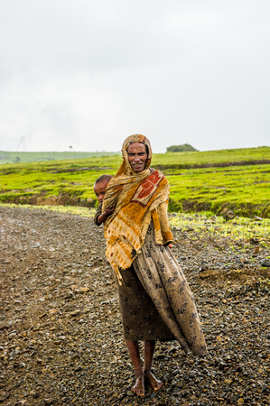 OMO, ETHIOPIA - SEPTEMBER 21, 2011: Unidentified Ethiopian woman and her baby on the back. People in Ethiopia suffer of poverty due to the unstable situation