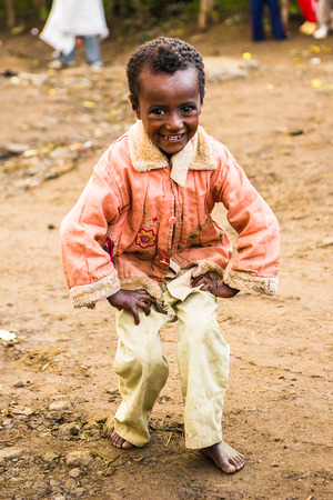LALIBELA, ETHIOPIA - SEPTEMBER 28, 2011:  Unidentified Ethiopian little boy dances for the camera wearing pink shirt and white trousers. People in Ethiopia suffer of poverty due to the unstable situation