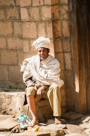 LALIBELA, ETHIOPIA - SEPTEMBER 28, 2011: Unidentified Ethiopian man sits at the porch of his house wearing old clothes. People in Ethiopia suffer of poverty due to the unstable situation