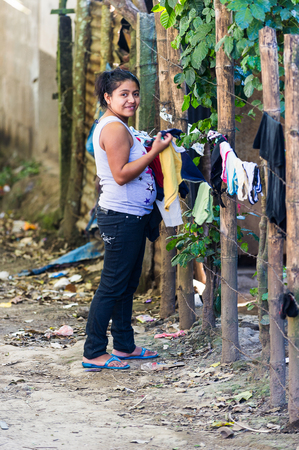 MANAGUA, NICARAGUA - JAN 6, 2012: Unidentified Nicaraguan woman hangs clothes. 69% of Nicaranguan people belong to the Mestizo ethnic group