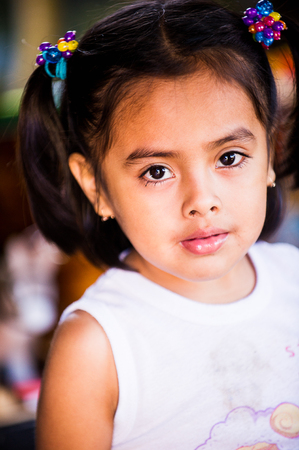 MANAGUA, NICARAGUA - JAN 6, 2012: Unidentified Nicaraguan little girl with pigtail. 69% of Nicaranguan people belong to the Mestizo ethnic group Editoriali