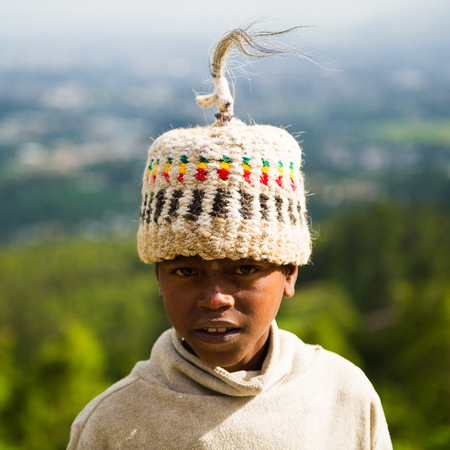 AKSUM, ETHIOPIA - SEP 29, 2011: Portrait of an unidentified Ethiopian cute little boy in a traditional hat in Ethiopia, Sep.29, 2011. People in Ethiopia suffer of poverty due to the unstable situation