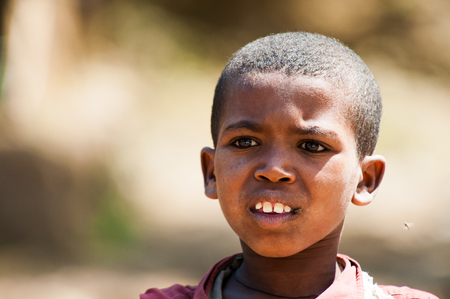 AKSUM, ETHIOPIA - SEP 28, 2011: Portrait of an unidentified Ethiopian cute little boy in old clothes in Ethiopia, Sep.28, 2011. People in Ethiopia suffer of poverty due to the unstable situation Stock Photo - 113978327