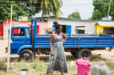 ACCRA, GHANA - MARCH 2, 2012: Unidentified Ghanaian woman stays in front of a truck in the street in Ghana. People of Ghana suffer of poverty due to the unstable economic situation