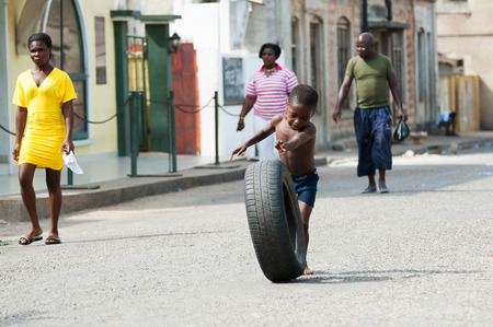 GHANA - MARCH 2, 2012: Unindentified Ghanaian boy plays with a car tire on the street in Ghana, on March 2nd, 2012. People in Ghana suffer from poverty due to the slow development of the country