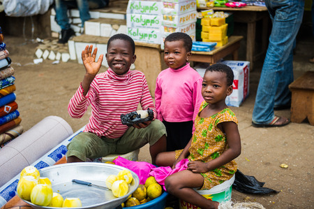 ACCRA, GHANA - MARCH 4, 2012: Unidentified Ghanaian children work at the market in Ghana. People of Ghana suffer of poverty due to the unstable economic situation Редакционное